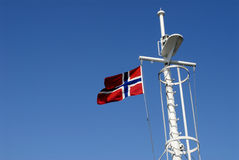 Norway Flag On Mast. Norway flag flying on the mast of a ferry. Isolated against a cloudless blue sky background royalty free stock images