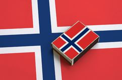 Norway flag is pictured on a matchbox that lies on a large flag.  stock photo