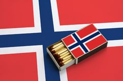 Norway flag is shown in an open matchbox, which is filled with matches and lies on a large flag.  royalty free stock photo