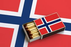 Norway flag is shown in an open matchbox, which is filled with matches and lies on a large flag.  royalty free stock photography