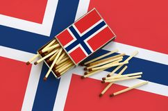 Norway flag is shown on an open matchbox, from which several matches fall and lies on a large flag.  stock images
