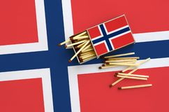 Norway flag is shown on an open matchbox, from which several matches fall and lies on a large flag.  royalty free stock photography