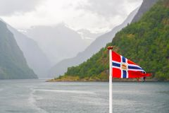 Norway flag waving on nature fjord of Norway. Norway flag waving on background of fjord Norway. Waving Norwegian flag on the fjord surrounded by mountains royalty free stock photo