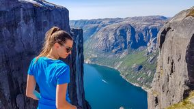 Norway - Girl in blue T-shirt and a fjord view. Girl wearing blue T-shirt looks down, past her shoulder. She is enjoying the fjord view in front of her. Stunning royalty free stock images