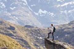 Norway hike, young woman traveler with backpack standing on the Stock Image