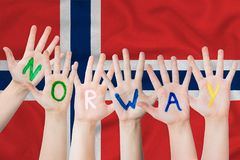 Norway inscription on the children`s hands against the background of a waving flag of the Norway.  royalty free stock photography