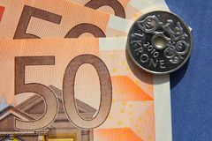 Euro banknotes 1 krone coin blue background. 1 Norway krone coin close-up on 50 euro banknotes on blue background Stock Photography