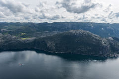 Norway Landscape. Preikestolen. River and Tourist Ferry in Background. Mountain. Blue sky. Royalty Free Stock Photos