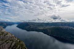 Norway Landscape. Preikestolen. River and Tourist Ferry in Background. Mountain. Blue sky. Royalty Free Stock Photography