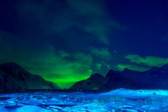 Snow-Covered Valley between Mountains and Aurora Borealis royalty free stock photos