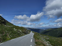 Norway road. Beautiful, straight summer road and Scandinavian landscape in Norway. Snow road Royalty Free Stock Image
