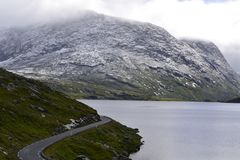 Norway road between fjords and rocky mountains. August snow in the north of Norway. Somewhere in Norway, beyond the Arctic Circle. Road going to the south stock images