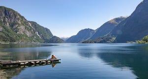 Sunbathing in front of Norwegian Fjord stock photos