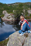 Norway. The thoughtful boy sits on a big stone at water Royalty Free Stock Photo