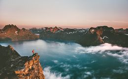Norway travel man tourist alone on the edge cliff stock photography