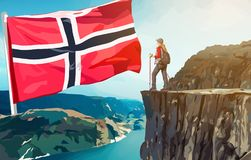 Norway travel. Preikestolen cliff with woman tourist and giant Norway flag. Travel concept Stock Photo