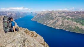 Norwegen - ein Junge mit einem wandernden Rucksack, der am Rand von Preikestolen sitzt stockfotos