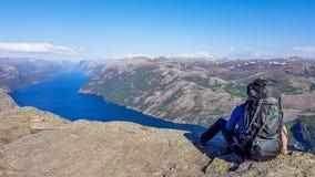 Norwegen - ein Junge mit einem wandernden Rucksack, der am Rand von Preikestolen sitzt stockfoto
