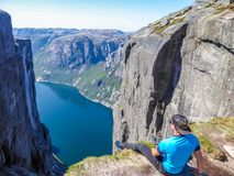 Norwegen - ein Mann, der am egde eines steilen Berges mit einer Fjordansicht sitzt lizenzfreie stockbilder