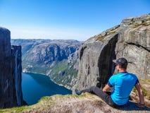 Norwegen - ein Mann, der am Rand eines steilen Berges mit einer Fjordansicht sitzt lizenzfreie stockfotos