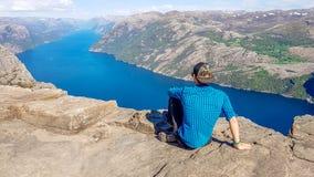 Norwegen - Junge, der auf einer steilen Klippe mit der Ansicht über Lysefjorden sitzt stockbild