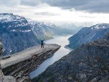 Norwegen - Stellung des jungen Mannes am Rand von Trolltunga stockfotos