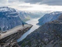 Norwegen - Stellung des jungen Mannes am Rand von Trolltunga lizenzfreie stockbilder