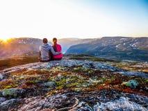 Norwegia - pary obsiadanie na dopatrywaniu i skale zmierzch fotografia stock