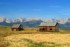 Norwegian 1700's style barns in Montana. Two 1700's style Norwegian barns stand in the fields of ranch lands with Montanas Battle Mountains in the background Royalty Free Stock Image