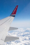 Norwegian airliner wing and snow clad French Alpes Royalty Free Stock Photos