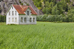 Norwegian antique traditional wooden house with grass and mountain. Horizontal royalty free stock photography