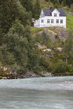 Norwegian antique traditional wooden house, river and hill Stock Photography