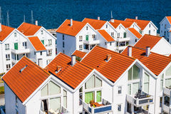 Norwegian architecture. Typical Norwegian architecture - wooden houses with sloping roofs located near sea coast Stock Photos