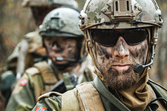 Norwegian Armed Forces soldiers. Norwegian Armed Forces Special Command FSK male and female soldiers closeup portrait. Radio and headset are on. Foreground Royalty Free Stock Photo