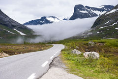 Norwegian asphalt road with hovering cloud between the mountains, on the road to Trollstigen, Norway Stock Image