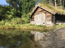 Norwegian boathouse. Norwegian timber boathouse with traditional grass roof Royalty Free Stock Image