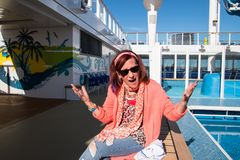 Woman on cruise ship eating breakfast on a bench upset that there were no tables left at the buffet. Norwegian Breakaway - June 1, 2018: Woman on cruise ship royalty free stock photography