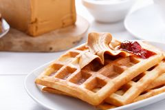 Norwegian brunost on white table. Homemade waffles with Scandinavian brown cheese and strawberry jam stock photography