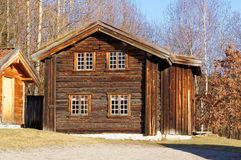 Norwegian building of round logs with small shutters Stock Photos