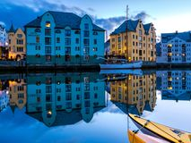City Scene with Traditional Houses and Boats Reflected in A Calm Canal at Night in Alesund. Image of Alesund after midnight in Summer. Alesund is a port town on stock image