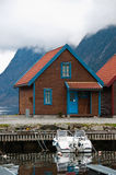 Norwegian cabin and the boat. The vetrical pucture of the ordinary norwegian cabin on shore royalty free stock images
