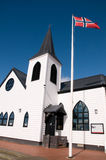 Norwegian Church at Cardiff Bay. The white wooden Norwegian church on the bay front at cardiff, with the flag of norway flying in the blue sky Royalty Free Stock Photography