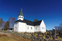Norwegian church and cemetry. Drangedal, Norway, March 21, 2015: Whitewashed Norwegian wooden church  with square tower surrounded by graves with similar Stock Image