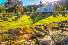 Roldal Stavkirke. Stavkirke of Roldal, norwegian wooden church, with square tower surrounded by graves with similar headstones and between them manicured lawn Royalty Free Stock Images