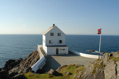 The Norwegian coast in summer. A white house and the Norwegian flag Stock Image