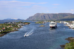 Norwegian coastal steamer leaving port of Bronnoysund. Cruiseship leaving port of Bronnoysund in Norway, mountains in the background Stock Photo