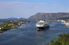 Norwegian coastal steamer leaving port of Bronnoysund. Cruiseship leaving port of Bronnoysund in Norway, mountains in the background Stock Images