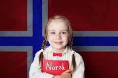 Norwegian concept with smiling kid student with book. Against the Norway flag background. Learn norwegian language royalty free stock image
