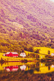 Norwegian country houses in the mountains on lake shore Royalty Free Stock Images