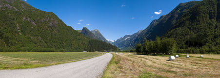 Norwegian countryside. A country road and some hay fields between green mountains in a beautiful norwegian countryside landscape Royalty Free Stock Photo
